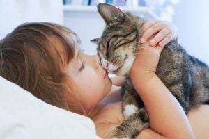 Cats make great pets. Girl kissing cat.