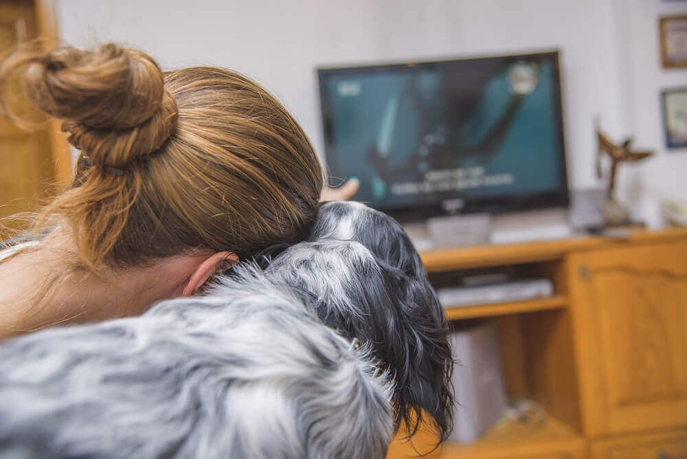 A woman watching TV with her dog.