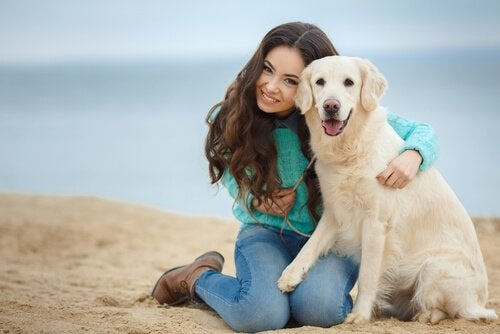 A girl and her dog on the beach.