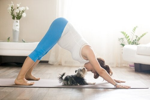 A lady doing yoga with her dog.