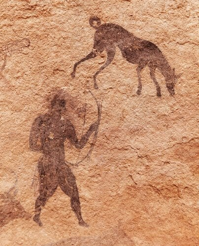 A cave painting of a hunter with his dog.