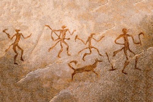 Some people and a dog in a cave painting.