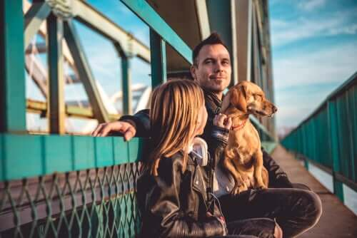 A man, a girl and their dog on a ferry.