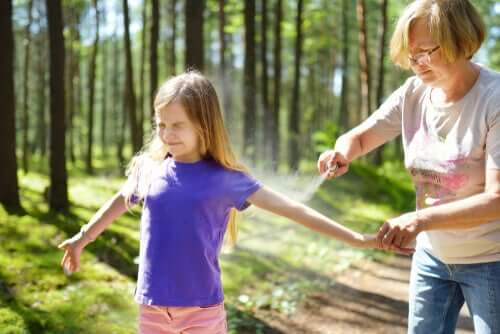 A girl getting bug spray to prevent diseases transmitted by ticks.