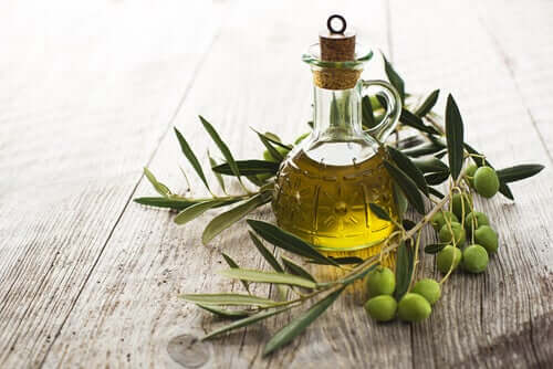 A bottle of olive oil sitting on a table with olive leaves and olives.