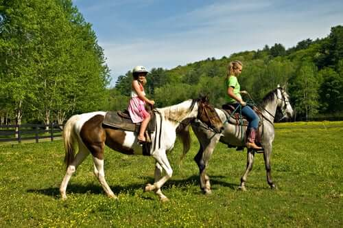 Girls riding horses in a field.