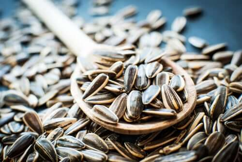 A picture of sunflower seeds and a wooden spoon.