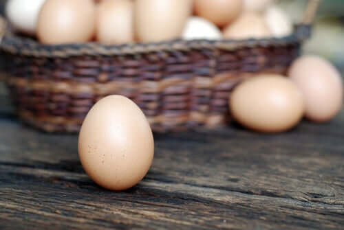 Some chicken eggs in a basket on a table.