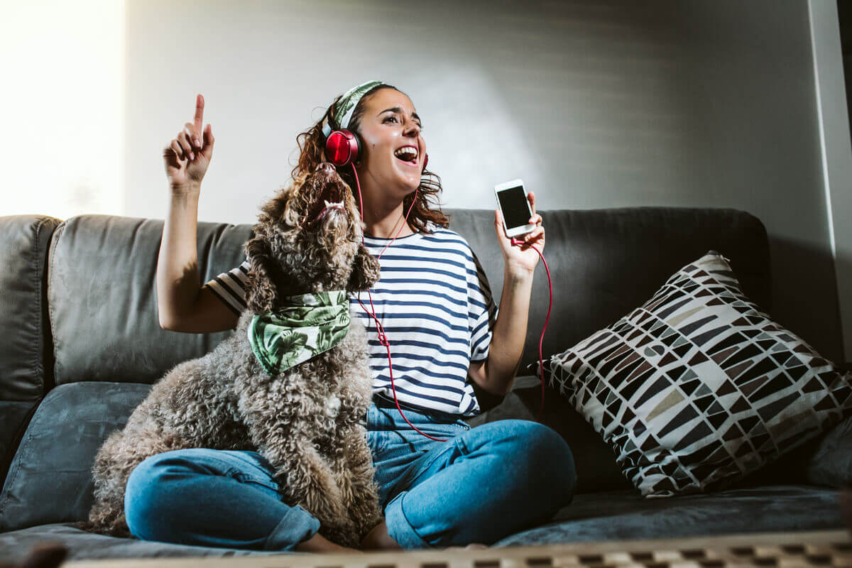 A woman sitting on the couch listening to music with her dog.