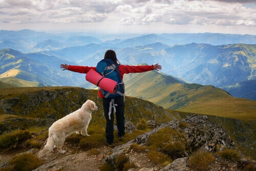 A woman and a dog on top of the world.