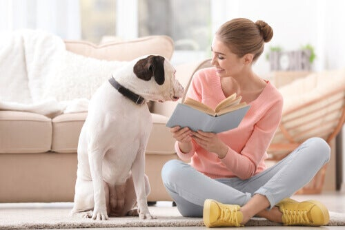 A woman reading a book to her dog.