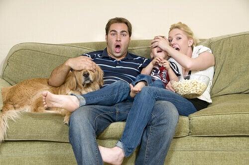 A family watch a movie on their sofa.